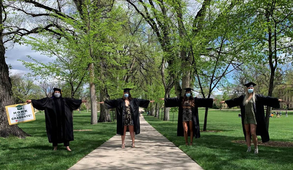 President McConnell joins Colorado State University graduates in regalia in a physically distanced celebration on the Oval at Colorado State University
