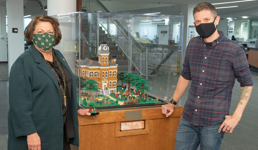 CSU President and Doug Cloud, assistant professor of English and master LEGO builder, stand in front of a LEGO rendition of Old Main in Morgan Library.